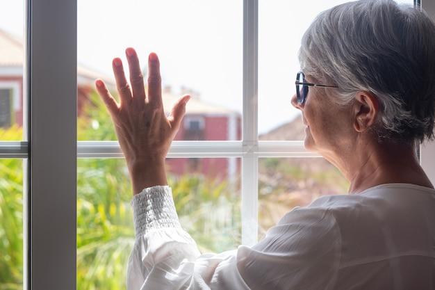 Ältere frau bleibt zu hause am fenster und schaut raus