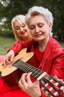 Ältere frau der nahaufnahme, die gitarre spielt