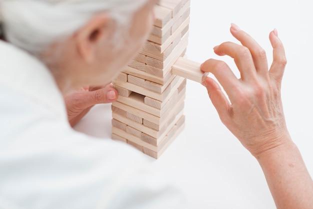 Ältere frau der nahaufnahme, die jenga spielt