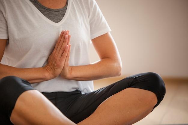 Ältere frau der nahaufnahme, die yoga tut