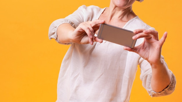 Ältere frau der nahaufnahme mit telefonmodell