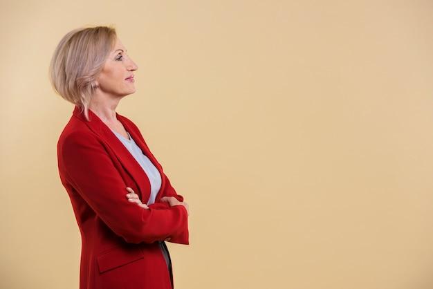 Ältere frau der seitenansicht, die weg mit kopienraum schaut