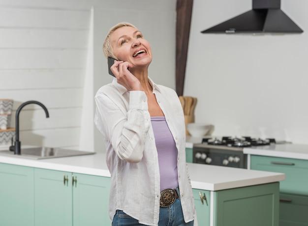 Ältere frau der vorderansicht, die an ihrem telefon spricht