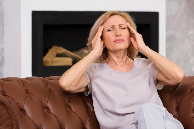 Ältere frau der vorderansicht, die schrecklichen kopfschmerzen hat