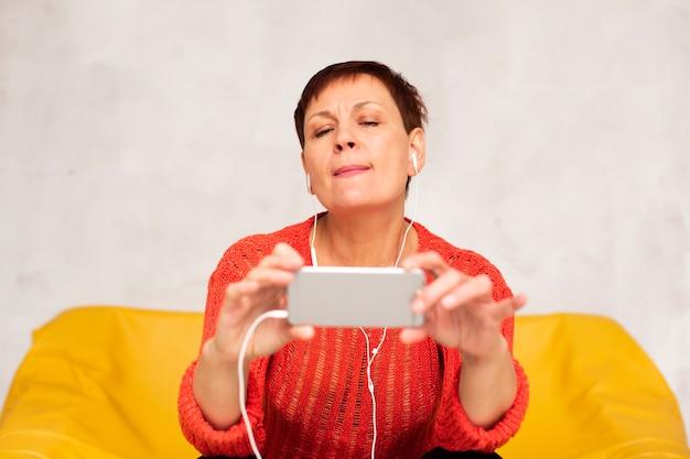 Ältere frau der vorderansicht, die selfies nimmt