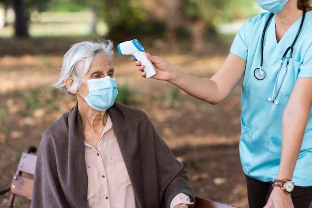 Ältere frau, deren temperatur von der krankenschwester überprüft wird