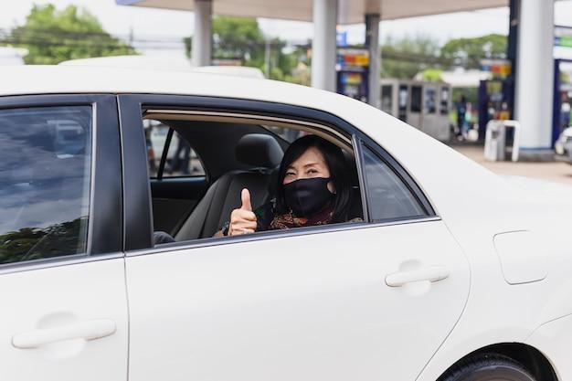 Ältere frau des coronavirus-pandemiekonzepts mit dem schutzmasken-daumen oben sitzen in einer auto-straßenfahrtreise.