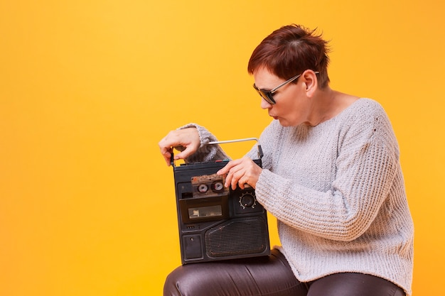 Ältere frau des hippies, die einen weinlesekassettenrecorder hält