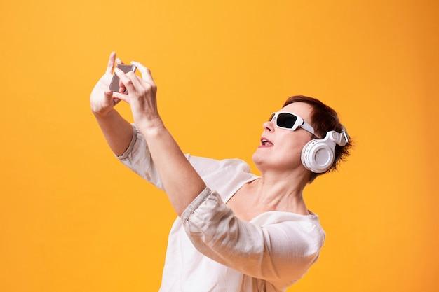 Ältere frau des hippies, die selfies nimmt