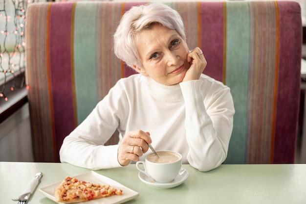 Ältere frau des hohen winkels am restaurant viel genießend