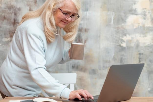 Ältere frau des hohen winkels, die vom haus arbeitet