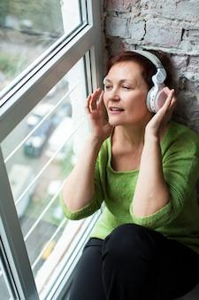 Ältere frau des hohen winkels nahe bei hörender musik des fensters