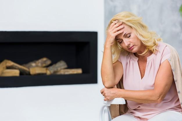 Ältere frau des mittleren schusses, die kopfschmerzen hat