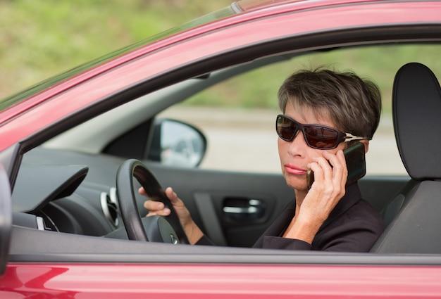 Ältere frau des modegeschäfts, die rotes auto mit telefon fährt