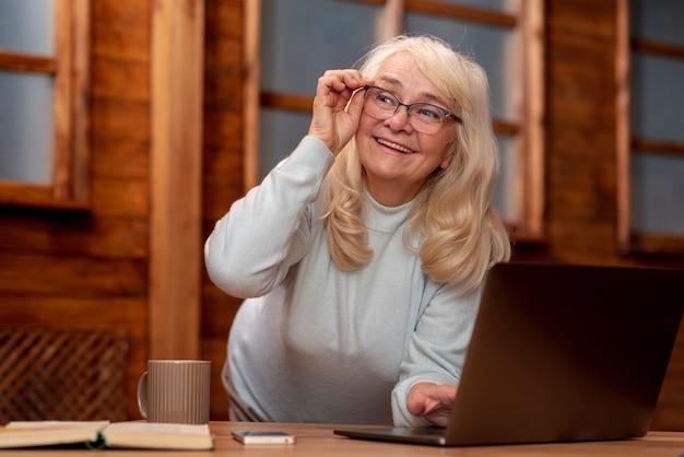 Ältere frau des niedrigen winkels, die an laptop arbeitet