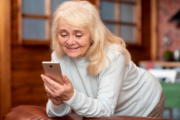 Ältere frau des niedrigen winkels, die auf mobile schaut