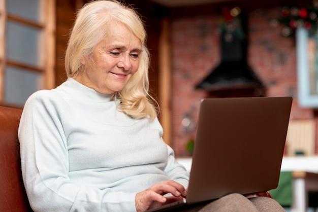 Ältere frau des niedrigen winkels, die laptop verwendet