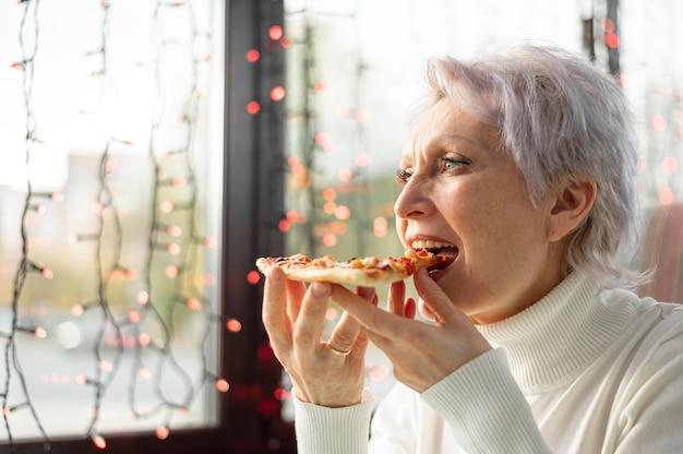 Ältere frau des niedrigen winkels, die pizzascheibe genießt