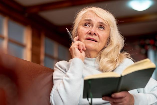 Ältere frau des niedrigen winkels, die tagesordnung hält