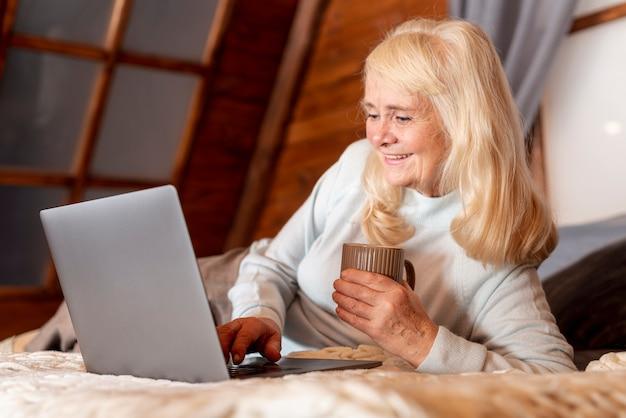 Ältere frau des niedrigen winkels im bett unter verwendung des laptops