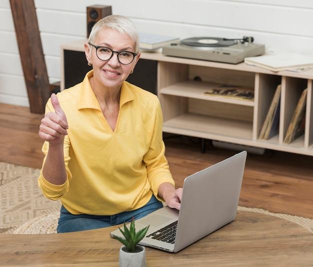 Ältere frau des smiley des hohen winkels, die einen laptop verwendet
