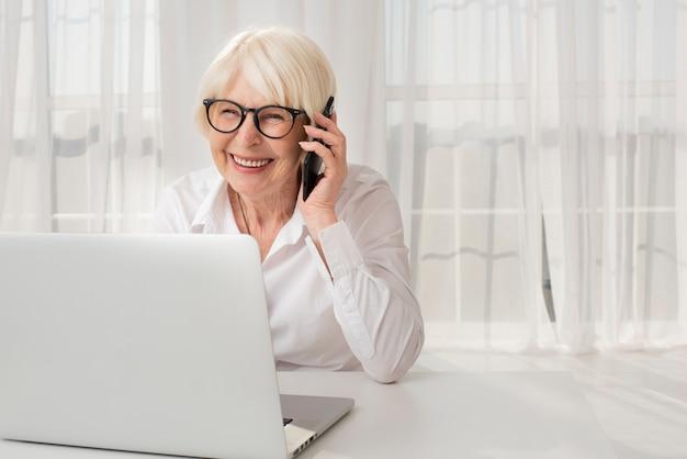 Ältere frau des smiley, die am telefon spricht