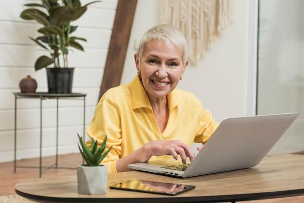 Ältere frau des smiley, die auf ihrem laptop schaut