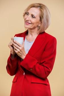 Ältere frau des smiley, die beim halten eines tasse kaffees weg schaut