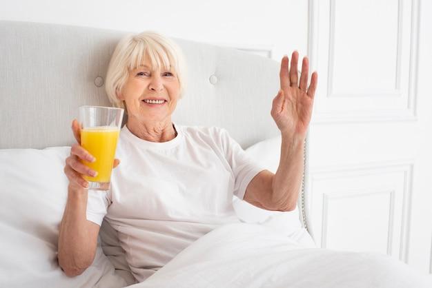 Ältere frau des smiley, die ein glas mit saft hält