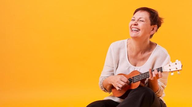 Ältere frau des smiley, die gitarre spielt