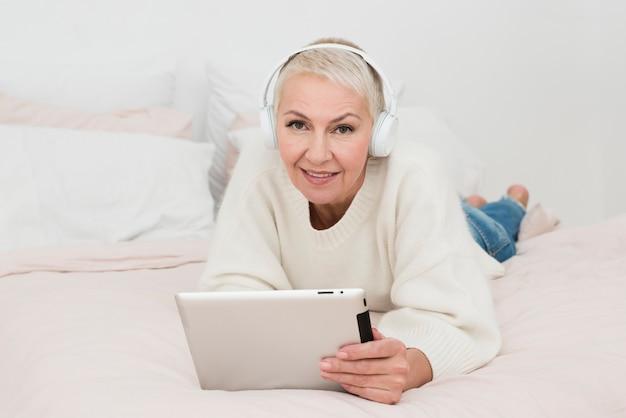 Ältere frau des smiley, die tablette hält und musik auf kopfhörern hört