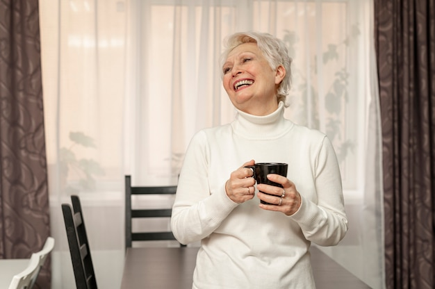 Ältere frau des smiley, die tasse kaffee hält