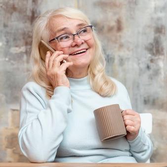 Ältere frau des smiley, die vom haus arbeitet