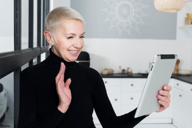 Ältere frau des smiley in der küche, die an der tablette wellenartig bewegt