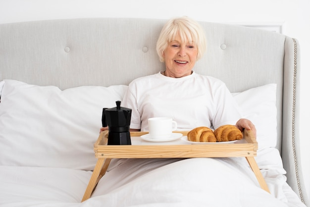 Ältere frau des smiley mit tellersegment im schlafzimmer