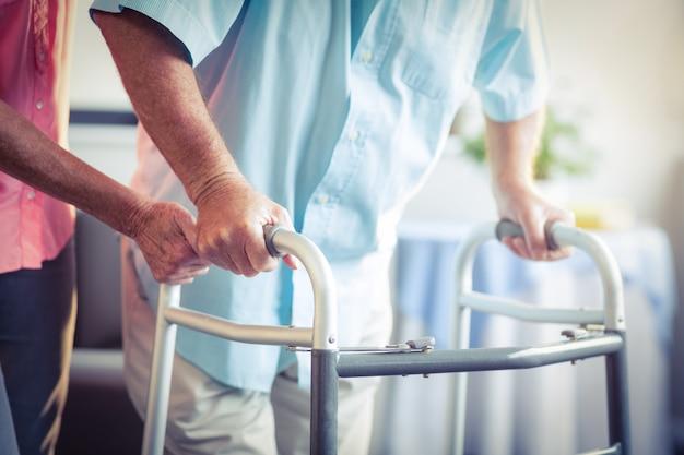 Ältere frau, die älterem mann hilft, mit wanderer zu gehen