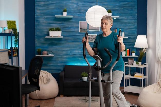 Ältere frau, die aerobic auf der fahrradmaschine im wohnzimmer für das wohlbefinden macht
