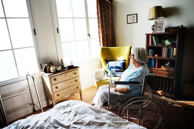 Ältere frau, die allein auf dem rollstuhl sitzt