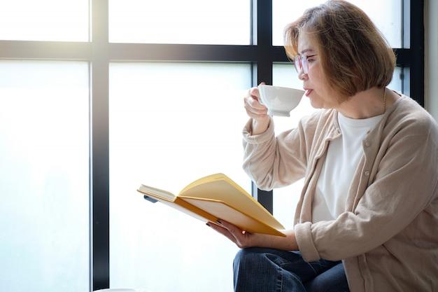 Ältere frau, die am fenster ein buch am entspannenden tag mit einem tasse kaffee liest.