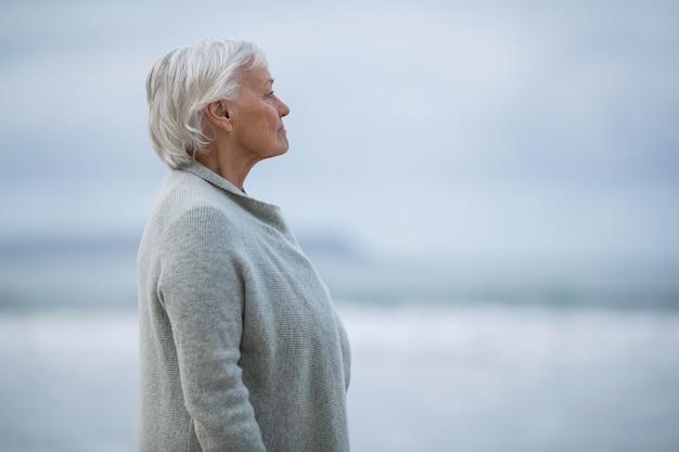 Ältere frau, die am strand steht