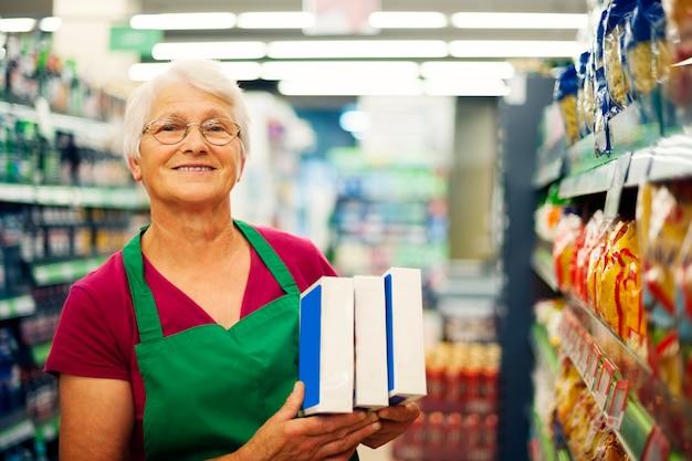Ältere frau, die am supermarkt arbeitet