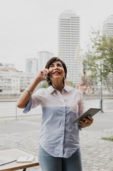Ältere frau, die am telefon auf städtischem hintergrund spricht
