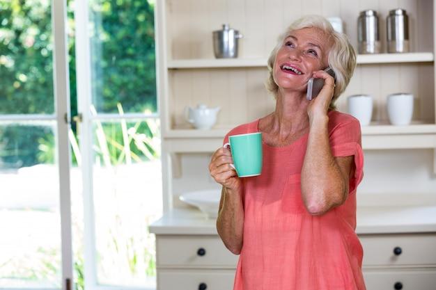 Ältere frau, die am telefon beim trinken des kaffees in der küche spricht