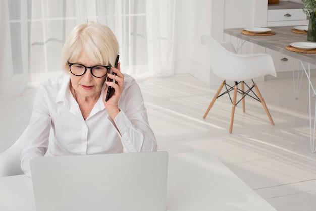 Ältere frau, die am telefon spricht