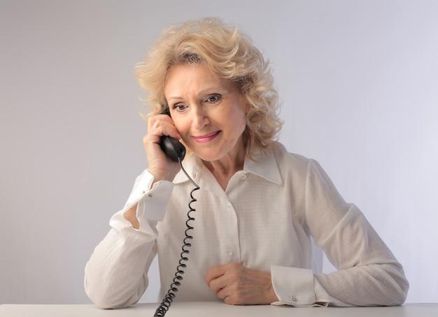 Ältere frau, die an einem klassischen telefon spricht