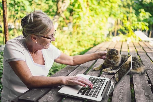 Ältere frau, die an einem laptop arbeitet