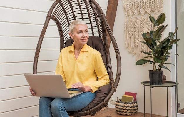Ältere frau, die an ihrem laptop arbeitet