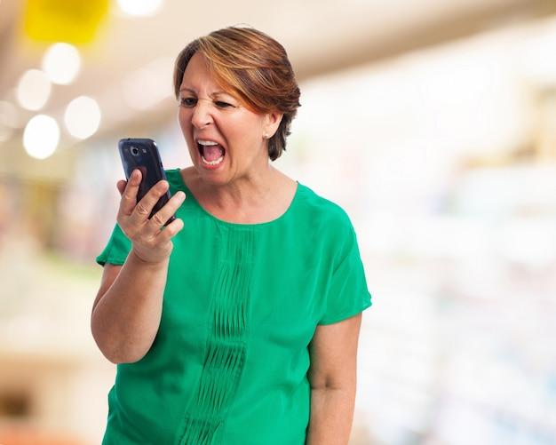 Ältere frau, die an ihrem telefon kreischt