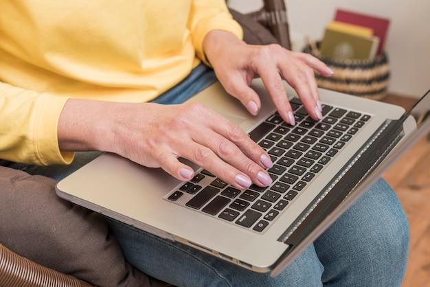 Ältere frau, die an ihrer laptopnahaufnahme arbeitet