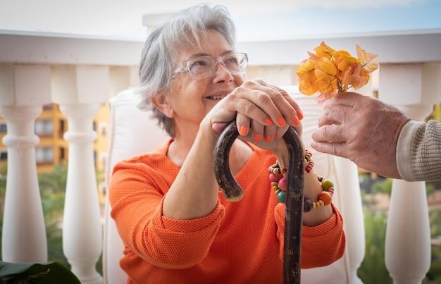 Ältere frau, die an rückenschmerzen leidet, sitzt mit den händen auf dem stock, während sie eine blume von ihrem ehemann erhält